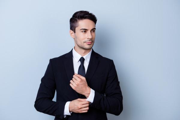 シャツの袖口を触る男性