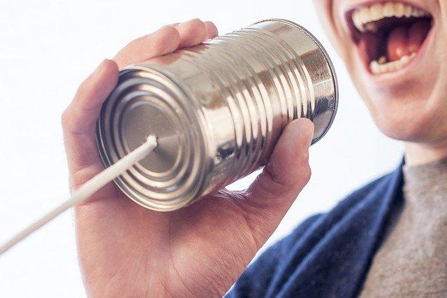 糸電話に話しかける男性