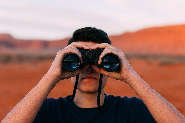 双眼鏡を覗くだ男性