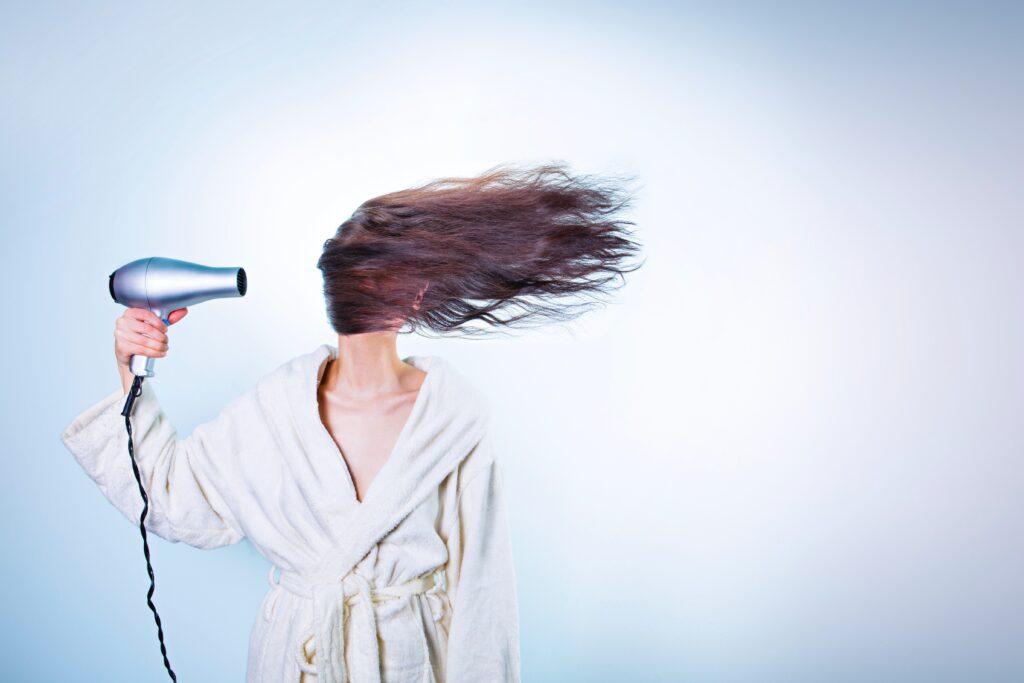 ドライヤーで髪を乾かす人
